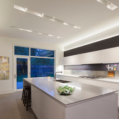 Trendy kitchen photo in Chicago with a double-bowl sink, flat-panel cabinets, white cabinets, white backsplash and stainless steel appliances