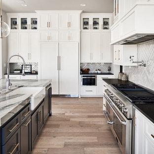Cette image montre une cuisine ouverte traditionnelle en L avec un évier de ferme, des portes de placard blanches, un plan de travail en quartz modifié, une crédence grise, une crédence en carreau de céramique, un électroménager en acier inoxydable, un sol en bois clair, un îlot central et un plan de travail multicolore.