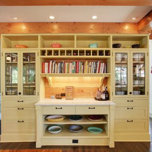 Traditional kitchen ideas - Example of a classic kitchen design in Seattle with glass-front cabinets and yellow cabinets