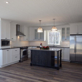 Inspiration for a mid-sized transitional l-shaped eat-in kitchen in Other with an undermount sink, shaker cabinets, yellow cabinets, granite benchtops, white splashback, subway tile splashback, stainless steel appliances, vinyl floors, with island and orange floor.