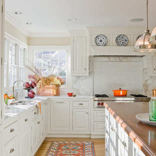 Inspiration for a timeless kitchen remodel in Boston with wood countertops, raised-panel cabinets, white cabinets, stone slab backsplash and stainless steel appliances