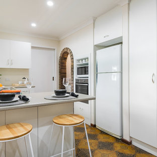 Small contemporary u-shaped kitchen in Perth with flat-panel cabinets, white cabinets, beige splashback, white appliances, a peninsula, orange floor and grey benchtop.