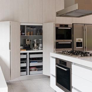Foto de cocina minimalista, de tamaño medio, con fregadero bajoencimera, armarios con paneles lisos, puertas de armario blancas, encimera de acrílico, electrodomésticos de acero inoxidable, suelo de baldosas de cerámica y una isla