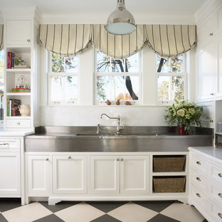 Inspiration for a large timeless u-shaped multicolored floor enclosed kitchen remodel in Minneapolis with recessed-panel cabinets, white cabinets, white backsplash, stainless steel appliances, a farmhouse sink, marble countertops, stone tile backsplash and an island