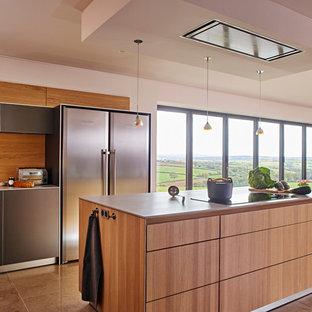 デヴォンの大きいコンテンポラリースタイルのおしゃれなキッチン (ドロップインシンク、フラットパネル扉のキャビネット、グレーのキャビネット、人工大理石カウンター、パネルと同色の調理設備、トラバーチンの床) の写真