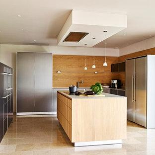 デヴォンの広いコンテンポラリースタイルのおしゃれなキッチン (ドロップインシンク、フラットパネル扉のキャビネット、グレーのキャビネット、人工大理石カウンター、パネルと同色の調理設備、トラバーチンの床) の写真