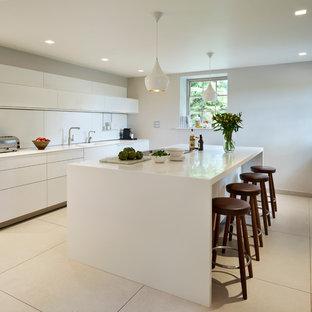 Modelo de cocina comedor minimalista con fregadero integrado, armarios con paneles lisos, puertas de armario blancas, salpicadero blanco, salpicadero de vidrio templado, suelo de baldosas de porcelana y una isla