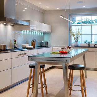 Inspiration for a contemporary kitchen in Wiltshire with flat-panel cabinets, white cabinets, stainless steel worktops and glass sheet splashback.
