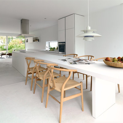 Mid-sized trendy galley concrete floor open concept kitchen photo in Melbourne with an undermount sink, flat-panel cabinets, white cabinets, stainless steel appliances, an island and white backsplash
