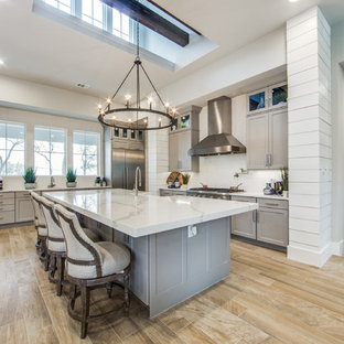 Inspiration for a large country eat-in kitchen in Austin with a farmhouse sink, shaker cabinets, grey cabinets, quartz benchtops, white splashback, ceramic splashback, stainless steel appliances, porcelain floors, multiple islands and beige floor.