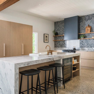 Design ideas for a country l-shaped kitchen in Sydney with a drop-in sink, flat-panel cabinets, light wood cabinets, grey splashback, black appliances, concrete floors, with island, beige floor and grey benchtop.