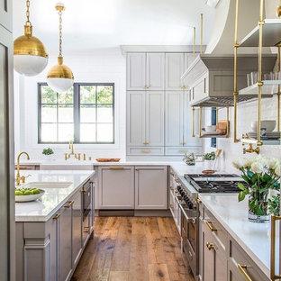 Mittelgroße Klassische Wohnküche mit Küchenrückwand in Weiß, Rückwand aus Metrofliesen, Küchengeräten aus Edelstahl, braunem Holzboden, Kücheninsel, Schrankfronten im Shaker-Stil und beigen Schränken in Los Angeles