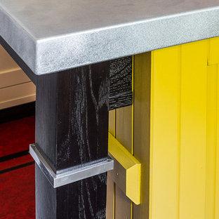 他の地域の中サイズのおしゃれなキッチン (アンダーカウンターシンク、シェーカースタイル扉のキャビネット、黄色いキャビネット、御影石カウンター、白いキッチンパネル、セラミックタイルのキッチンパネル、白い調理設備、リノリウムの床、赤い床、黒いキッチンカウンター) の写真