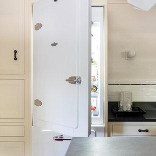 Mittelgroße Urige Küche in L-Form mit Vorratsschrank, Unterbauwaschbecken, Schrankfronten im Shaker-Stil, gelben Schränken, Granit-Arbeitsplatte, Küchenrückwand in Weiß, Rückwand aus Keramikfliesen, weißen Elektrogeräten, Linoleum, Kücheninsel, rotem Boden und schwarzer Arbeitsplatte in Sonstige