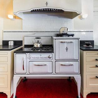 サクラメントの中くらいのおしゃれなキッチン (アンダーカウンターシンク、シェーカースタイル扉のキャビネット、黄色いキャビネット、御影石カウンター、白いキッチンパネル、セラミックタイルのキッチンパネル、白い調理設備、リノリウムの床、赤い床、黒いキッチンカウンター) の写真