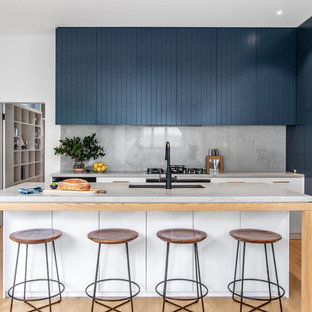 This is an example of a contemporary galley kitchen in Sydney with an undermount sink, blue cabinets, with island, grey benchtop, marble benchtops, multi-coloured splashback, marble splashback, black appliances and light hardwood floors.