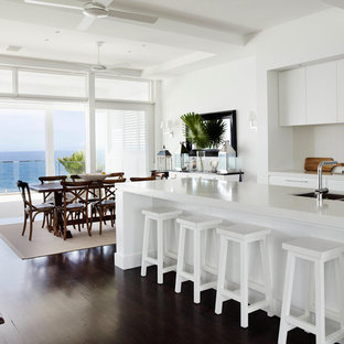 Photo of a mid-sized beach style eat-in kitchen in Sydney with flat-panel cabinets, white cabinets, quartz benchtops, dark hardwood floors and white benchtop.