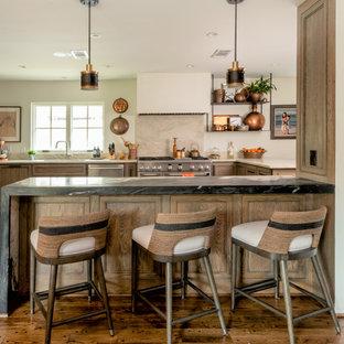 Klassische Küche in U-Form mit Unterbauwaschbecken, Schrankfronten mit vertiefter Füllung, hellbraunen Holzschränken, Küchenrückwand in Beige, Rückwand aus Stein, Küchengeräten aus Edelstahl, braunem Holzboden, Halbinsel, braunem Boden und schwarzer Arbeitsplatte in Houston