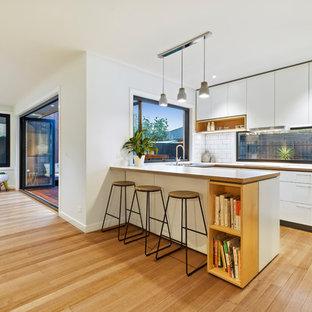 Inredning av ett modernt litet vit vitt kök, med en nedsänkt diskho, luckor med upphöjd panel, vita skåp, marmorbänkskiva, vitt stänkskydd, stänkskydd i keramik, rostfria vitvaror, ljust trägolv, en köksö och gult golv