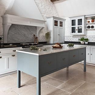 ウィルトシャーの大きいカントリー風おしゃれなキッチン (落し込みパネル扉のキャビネット、白いキャビネット、大理石カウンター、グレーのキッチンパネル、大理石の床、トラバーチンの床、ベージュの床) の写真