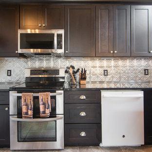 ダラスの小さいエクレクティックスタイルのおしゃれなキッチン (シングルシンク、シェーカースタイル扉のキャビネット、濃色木目調キャビネット、御影石カウンター、メタリックのキッチンパネル、メタルタイルのキッチンパネル、シルバーの調理設備、磁器タイルの床、アイランドなし、ベージュの床) の写真