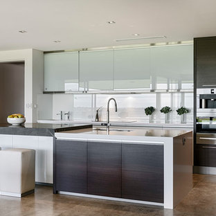 Contemporary kitchen designs - Trendy kitchen photo in Perth with glass-front cabinets, stainless steel cabinets, white backsplash, glass sheet backsplash, stainless steel appliances and an island