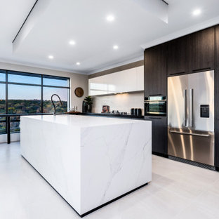 Photo of a large contemporary galley kitchen in Perth with an undermount sink, flat-panel cabinets, black cabinets, white splashback, stainless steel appliances, with island, white floor and black benchtop.