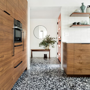 This is an example of a small midcentury u-shaped kitchen/diner in Portland with a submerged sink, flat-panel cabinets, dark wood cabinets, engineered stone countertops, white splashback, ceramic splashback, integrated appliances, terrazzo flooring, black floors and white worktops.