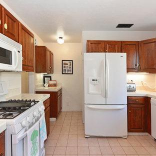サンディエゴの中サイズの地中海スタイルのおしゃれなキッチン (ダブルシンク、レイズドパネル扉のキャビネット、中間色木目調キャビネット、タイルカウンター、ベージュキッチンパネル、セラミックタイルのキッチンパネル、白い調理設備、セラミックタイルの床、アイランドなし) の写真