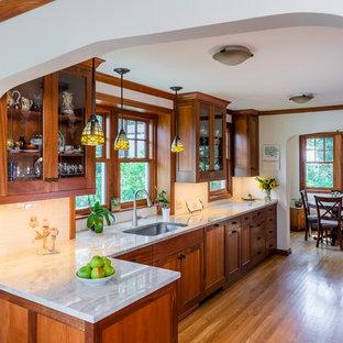 Exemple d'une cuisine craftsman fermée et de taille moyenne avec un évier encastré, un placard à porte shaker, des portes de placard en bois sombre, une crédence blanche, une crédence en carrelage métro, un sol en bois brun, aucun îlot, un sol marron, un plan de travail gris et un plan de travail en quartz modifié.