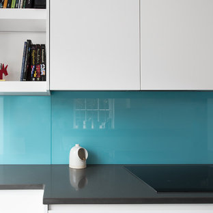 Mid-sized modern galley eat-in kitchen in London with a double-bowl sink, flat-panel cabinets, white cabinets, solid surface benchtops, blue splashback, glass sheet splashback, stainless steel appliances, porcelain floors and no island.