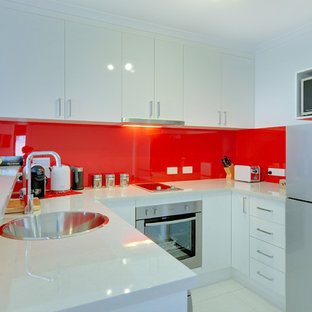 Small modern eat-in kitchen inspiration - Example of a small minimalist u-shaped ceramic floor eat-in kitchen design in Hobart with a drop-in sink, white cabinets, laminate countertops, red backsplash, glass sheet backsplash, stainless steel appliances and a peninsula