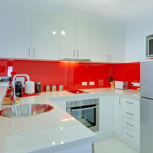 Esempio di una piccola cucina minimalista con lavello da incasso, ante bianche, top in laminato, paraspruzzi rosso, paraspruzzi con lastra di vetro, elettrodomestici in acciaio inossidabile, pavimento con piastrelle in ceramica e penisola