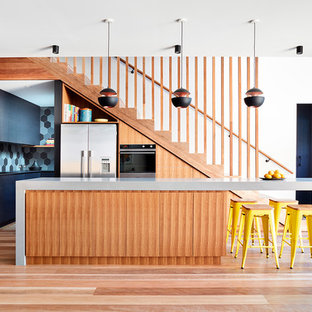 Inspiration for a mid-sized contemporary l-shaped open plan kitchen in Melbourne with flat-panel cabinets, solid surface benchtops, porcelain splashback, stainless steel appliances, medium hardwood floors, with island, brown floor, grey cabinets, multi-coloured splashback and grey benchtop.