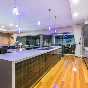 Large contemporary galley eat-in kitchen in Perth with a drop-in sink, flat-panel cabinets, dark wood cabinets, quartz benchtops, metallic splashback, glass sheet splashback, stainless steel appliances, medium hardwood floors and with island.