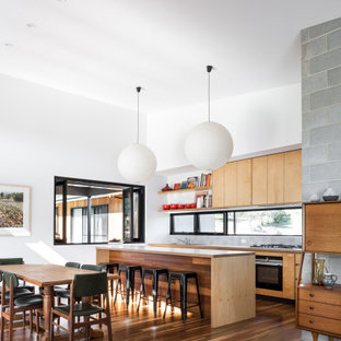 Contemporary galley open plan kitchen in Other with flat-panel cabinets, medium wood cabinets, black appliances, dark hardwood floors, with island and brown floor.