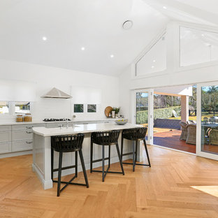 Design ideas for an expansive country l-shaped open plan kitchen in Wollongong with a farmhouse sink, shaker cabinets, grey cabinets, quartz benchtops, white splashback, ceramic splashback, stainless steel appliances, with island, medium hardwood floors, brown floor and white benchtop.