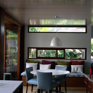 Idéer för små 60 tals linjära vitt kök och matrum, med en undermonterad diskho, släta luckor, skåp i mörkt trä, marmorbänkskiva, stänkskydd med metallisk yta, spegel som stänkskydd, svarta vitvaror, ljust trägolv, en köksö och gult golv