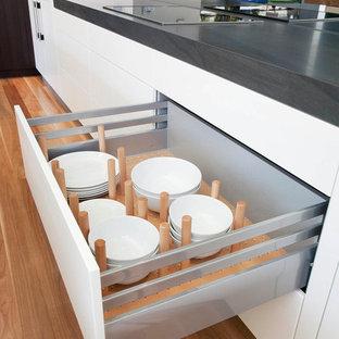 Modern inredning av ett mycket stort kök, med en undermonterad diskho, släta luckor, beige skåp, marmorbänkskiva, grått stänkskydd, glaspanel som stänkskydd, svarta vitvaror, mellanmörkt trägolv och en köksö