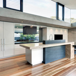 Design ideas for an expansive modern l-shaped eat-in kitchen in Sydney with an undermount sink, flat-panel cabinets, beige cabinets, marble benchtops, grey splashback, glass sheet splashback, medium hardwood floors and with island.