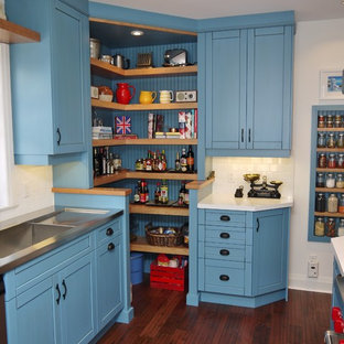 This is an example of a country kitchen in Toronto with an integrated sink, blue cabinets, stainless steel benchtops, white splashback, subway tile splashback, stainless steel appliances and open cabinets.