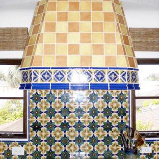 中サイズの地中海スタイルのおしゃれなキッチン (アイランドなし、フラットパネル扉のキャビネット、濃色木目調キャビネット、タイルカウンター、シルバーの調理設備の、ドロップインシンク、マルチカラーのキッチンパネル、モザイクタイルのキッチンパネル) の写真