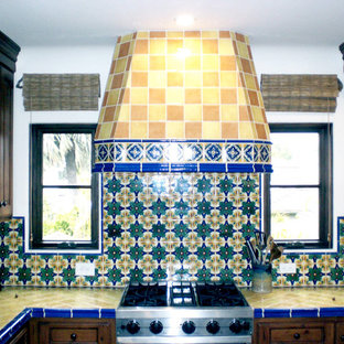 Mid-sized mediterranean u-shaped eat-in kitchen in Santa Barbara with no island, dark wood cabinets, tile benchtops, stainless steel appliances, a drop-in sink, multi-coloured splashback and mosaic tile splashback.