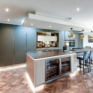 Große Moderne Küche in L-Form mit Unterbauwaschbecken, flächenbündigen Schrankfronten, grauen Schränken, Rückwand aus Spiegelfliesen, Küchengeräten aus Edelstahl, hellem Holzboden, Kücheninsel, braunem Boden und schwarzer Arbeitsplatte in Hertfordshire