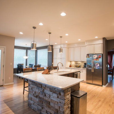 Large eclectic single-wall light wood floor and beige floor open concept kitchen photo in Denver with an undermount sink, raised-panel cabinets, white cabinets, quartz countertops, beige backsplash, glass tile backsplash, stainless steel appliances and an island