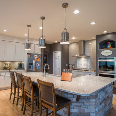 Example of a large eclectic single-wall light wood floor and beige floor open concept kitchen design in Denver with an undermount sink, raised-panel cabinets, white cabinets, quartz countertops, beige backsplash, glass tile backsplash, stainless steel appliances and an island