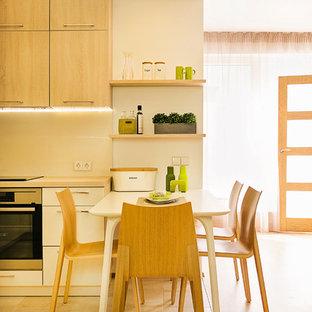 他の地域の小さいモダンスタイルのおしゃれなキッチン (ドロップインシンク、フラットパネル扉のキャビネット、淡色木目調キャビネット、大理石カウンター、ベージュキッチンパネル、ガラス板のキッチンパネル、シルバーの調理設備、セラミックタイルの床) の写真