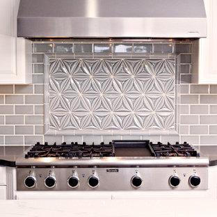 Idéer för ett mellanstort svart kök, med en rustik diskho, luckor med upphöjd panel, vita skåp, träbänkskiva, grått stänkskydd, stänkskydd i glaskakel, rostfria vitvaror, mellanmörkt trägolv, en köksö och brunt golv