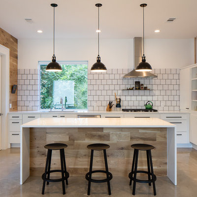 Inspiration for a mid-sized country u-shaped concrete floor open concept kitchen remodel in Austin with an undermount sink, flat-panel cabinets, white cabinets, white backsplash, stainless steel appliances, an island, solid surface countertops, porcelain backsplash and white countertops