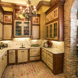 Ejemplo de cocina mediterránea con fregadero bajoencimera, armarios con paneles con relieve, puertas de armario con efecto envejecido, salpicadero beige y suelo de ladrillo